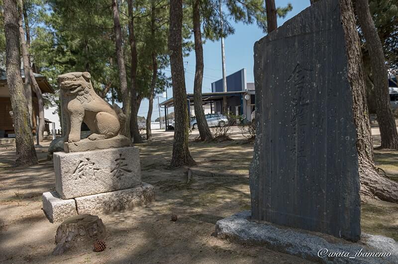 丸みを帯びた狛犬と石碑